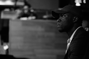 Nosa Eguae Professional Speaker MC Educator Mentor and Athlete Transitional Consultant Black Man in SUit and baseball cap thinking black and white